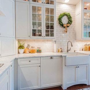 Cette image montre une cuisine victorienne avec un évier de ferme, un placard à porte vitrée, des portes de placard blanches, une crédence blanche et une crédence en carrelage métro.