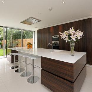他の地域のコンテンポラリースタイルのおしゃれなキッチン (フラットパネル扉のキャビネット、濃色木目調キャビネット、白い床) の写真