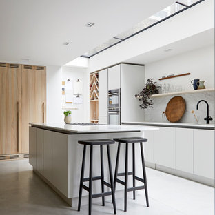 Large contemporary galley open plan kitchen in London with an integrated sink, flat-panel cabinets, grey cabinets, marble worktops, grey splashback, marble splashback, black appliances, concrete flooring, an island, grey floors and grey worktops.