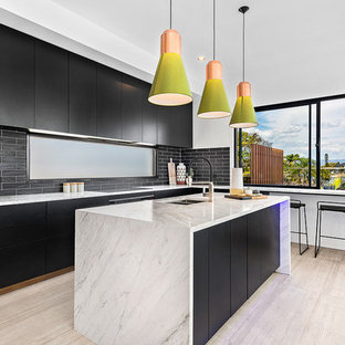 Photo of a large contemporary single-wall eat-in kitchen in Brisbane with an undermount sink, flat-panel cabinets, black cabinets, black splashback, subway tile splashback, with island, beige floor, granite benchtops, stainless steel appliances and porcelain floors.