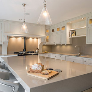 Transitional l-shaped open plan kitchen in Dublin with a double-bowl sink, recessed-panel cabinets, white cabinets, soapstone benchtops, beige splashback, glass sheet splashback, panelled appliances, ceramic floors and with island.