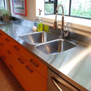 На фото: кухни в стиле ретро с монолитной раковиной, плоскими фасадами, оранжевыми фасадами, столешницей из нержавеющей стали, фартуком цвета металлик, фартуком из металлической плитки и техникой из нержавеющей стали