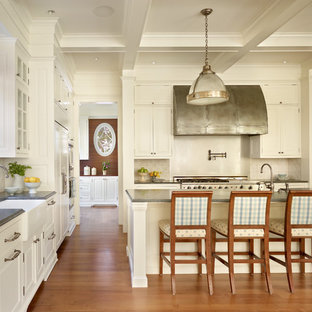 Example of a classic kitchen design in Seattle with a farmhouse sink, raised-panel cabinets, white cabinets, white backsplash and stainless steel appliances