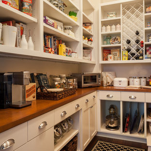 Large traditional l-shaped kitchen pantry in Seattle with recessed-panel cabinets, white cabinets, wood worktops, white splashback, ceramic splashback, integrated appliances and dark hardwood flooring.