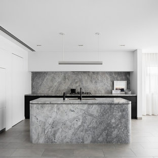 Photo of a modern l-shaped kitchen in Sydney with an undermount sink, flat-panel cabinets, black cabinets, grey splashback, marble splashback, panelled appliances, with island, grey floor and grey benchtop.