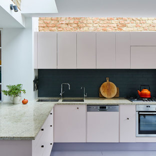 Design ideas for a contemporary l-shaped kitchen in London with a double-bowl sink, flat-panel cabinets, beige cabinets, black splashback, metro tiled splashback, stainless steel appliances, a breakfast bar and multicoloured worktops.