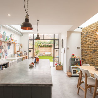 This is an example of an industrial galley kitchen in London with a belfast sink, grey cabinets, multi-coloured splashback, cement tile splashback, stainless steel appliances, an island, grey floors and grey worktops.