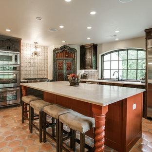 Foto på ett stort medelhavsstil l-kök, med en undermonterad diskho, bänkskiva i kvarts, flerfärgad stänkskydd, stänkskydd i porslinskakel, rostfria vitvaror, klinkergolv i terrakotta, en köksö, skåp i shakerstil och skåp i slitet trä