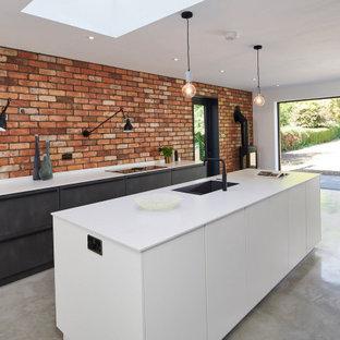 Idéer för att renovera ett industriellt vit vitt kök med öppen planlösning, med en enkel diskho, släta luckor, svarta skåp, stänkskydd i tegel, betonggolv, en köksö och grått golv