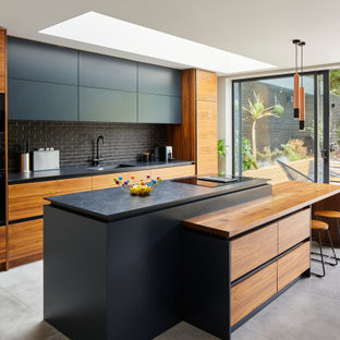 Inspiration for a contemporary kitchen in London with an integrated sink, flat-panel cabinets, black cabinets, black splashback, metro tiled splashback, black appliances, an island, grey floors and black worktops.