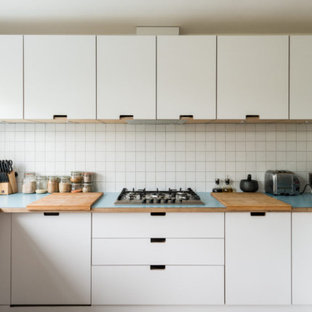 Mid-sized midcentury u-shaped eat-in kitchen in London with a double-bowl sink, flat-panel cabinets, white cabinets, wood benchtops, white splashback, cement tile splashback, stainless steel appliances, medium hardwood floors, no island, brown floor and blue benchtop.