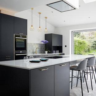ケントの大きいコンテンポラリースタイルのおしゃれなキッチン (ドロップインシンク、フラットパネル扉のキャビネット、青いキャビネット、人工大理石カウンター、メタリックのキッチンパネル、ガラスタイルのキッチンパネル、黒い調理設備、磁器タイルの床、グレーの床、白いキッチンカウンター) の写真