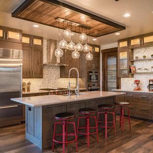 Offene, Mittelgroße Rustikale Küche in L-Form mit Landhausspüle, Schrankfronten mit vertiefter Füllung, Mineralwerkstoff-Arbeitsplatte, Rückwand aus Steinfliesen, Küchengeräten aus Edelstahl, braunem Holzboden, Kücheninsel, braunem Boden, hellbraunen Holzschränken, Küchenrückwand in Beige und weißer Arbeitsplatte in Denver