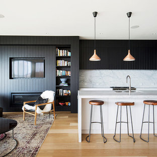Design ideas for a contemporary l-shaped open plan kitchen in Sydney with an undermount sink, beaded inset cabinets, black cabinets, white splashback, stainless steel appliances, light hardwood floors and with island.