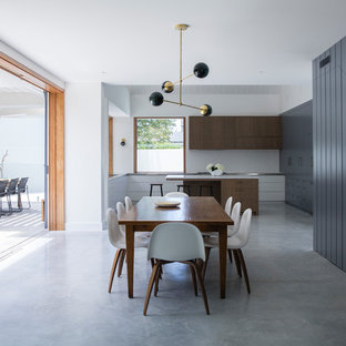 This is an example of a beach style u-shaped eat-in kitchen in Sydney with flat-panel cabinets, white cabinets, stainless steel benchtops, white splashback, subway tile splashback, concrete floors, with island, grey floor and grey benchtop.
