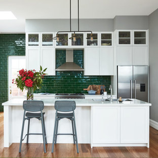 Inspiration for a transitional galley open plan kitchen in Sydney with a double-bowl sink, shaker cabinets, white cabinets, green splashback, subway tile splashback, stainless steel appliances, medium hardwood floors, with island, brown floor and white benchtop.