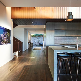 Design ideas for a contemporary kitchen in Sydney with a double-bowl sink, flat-panel cabinets, grey cabinets, grey splashback, dark hardwood floors, with island, brown floor and grey benchtop.