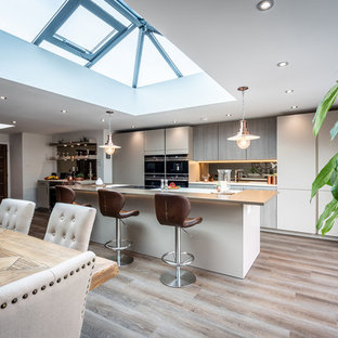 Photo of a contemporary galley kitchen/diner in Hampshire with flat-panel cabinets, beige cabinets, mirror splashback, black appliances, light hardwood flooring, an island, beige floors and white worktops.
