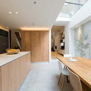 Пример оригинального дизайна: огромная параллельная кухня-гостиная в современном стиле с плоскими фасадами, светлыми деревянными фасадами, техникой из нержавеющей стали, бетонным полом, островом, серым полом, накладной раковиной, столешницей из акрилового камня, белым фартуком, фартуком из мрамора и белой столешницей