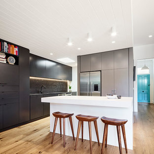 Photo of a contemporary galley kitchen in Melbourne with flat-panel cabinets, black cabinets, stainless steel appliances, light hardwood floors and an island.