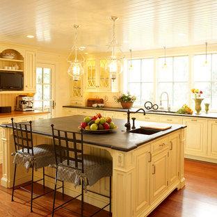 Geschlossene Klassische Küche in L-Form mit Unterbauwaschbecken, Kassettenfronten, gelben Schränken, Speckstein-Arbeitsplatte, Küchenrückwand in Gelb, Rückwand aus Keramikfliesen, Küchengeräten aus Edelstahl, braunem Holzboden und Kücheninsel in Philadelphia