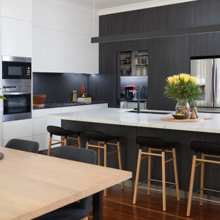 Inspiration for a contemporary l-shaped kitchen in Brisbane with an undermount sink, flat-panel cabinets, black cabinets, black splashback, mosaic tile splashback, stainless steel appliances, dark hardwood floors, with island, brown floor and white benchtop.