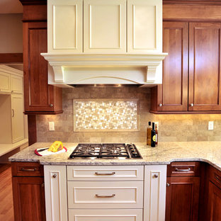 Eat-in kitchen - large traditional l-shaped eat-in kitchen idea in Milwaukee with an undermount sink, beaded inset cabinets, medium tone wood cabinets, granite countertops, beige backsplash, mosaic tile backsplash and paneled appliances