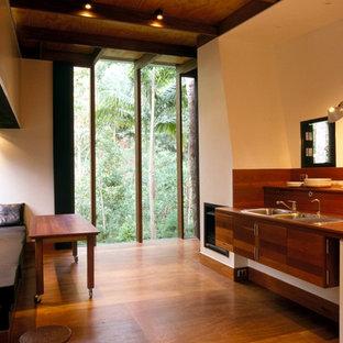 Réalisation d'une cuisine linéaire ethnique de taille moyenne avec un évier 2 bacs, des portes de placard en bois sombre, un plan de travail en bois et un sol en contreplaqué.