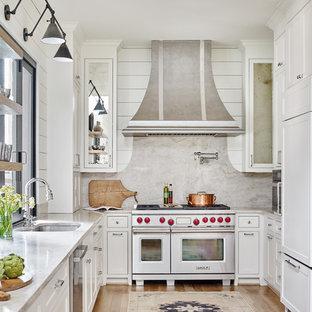 アトランタの中くらいのカントリー風おしゃれなキッチン (アンダーカウンターシンク、白いキャビネット、石スラブのキッチンパネル、無垢フローリング、茶色い床、落し込みパネル扉のキャビネット、大理石カウンター、白いキッチンパネル、パネルと同色の調理設備、白いキッチンカウンター、アイランドなし) の写真