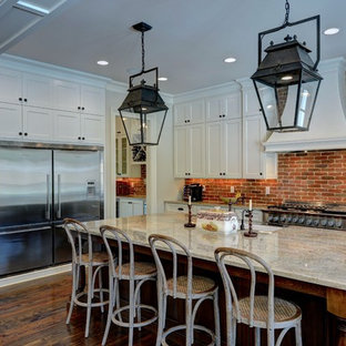 Farmhouse kitchen ideas - Country l-shaped dark wood floor and brown floor kitchen photo in Atlanta with a farmhouse sink, shaker cabinets, white cabinets, granite countertops, brick backsplash, stainless steel appliances, an island, red backsplash and gray countertops
