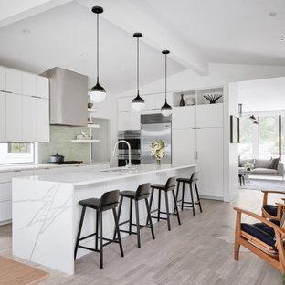 Diseño de cocina comedor en L, contemporánea, pequeña, con armarios con paneles lisos, puertas de armario blancas, salpicadero verde, electrodomésticos de acero inoxidable, suelo de madera clara, una isla, encimeras blancas, fregadero bajoencimera y suelo gris