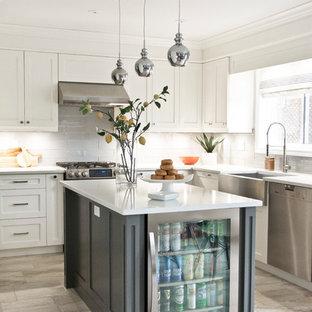 Modelo de cocina en L, tradicional renovada, con fregadero sobremueble, armarios estilo shaker, puertas de armario blancas, salpicadero verde, salpicadero de azulejos de vidrio, electrodomésticos de acero inoxidable, una isla y suelo gris