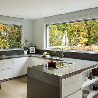 Immagine di una cucina ad U minimal di medie dimensioni con lavello sottopiano, ante lisce, ante bianche, paraspruzzi grigio, elettrodomestici in acciaio inossidabile, parquet chiaro e penisola