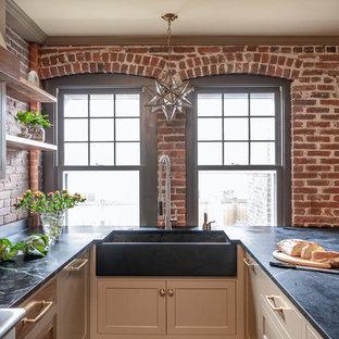 Mittelgroße Country Küche in L-Form mit Schrankfronten im Shaker-Stil, braunen Schränken, Küchengeräten aus Edelstahl, Kücheninsel, schwarzer Arbeitsplatte, Vorratsschrank, Unterbauwaschbecken, Küchenrückwand in Rot, Rückwand aus Backstein, Schieferboden und buntem Boden in Boston