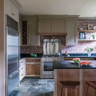 ボストンの中サイズのカントリー風おしゃれなキッチン (シェーカースタイル扉のキャビネット、茶色いキャビネット、シルバーの調理設備の、黒いキッチンカウンター、アンダーカウンターシンク、赤いキッチンパネル、レンガのキッチンパネル、スレートの床、マルチカラーの床) の写真