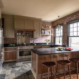 ボストンのカントリー風おしゃれなキッチン (アンダーカウンターシンク、シェーカースタイル扉のキャビネット、茶色いキャビネット、赤いキッチンパネル、レンガのキッチンパネル、シルバーの調理設備の、スレートの床、マルチカラーの床、黒いキッチンカウンター) の写真