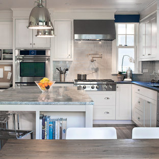 Design ideas for a large transitional l-shaped eat-in kitchen in Boston with an undermount sink, beaded inset cabinets, white cabinets, quartzite benchtops, blue splashback, porcelain splashback, stainless steel appliances, medium hardwood floors and with island.
