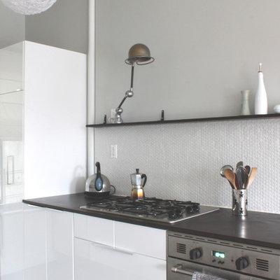 Minimalist kitchen photo in New York with flat-panel cabinets and white backsplash