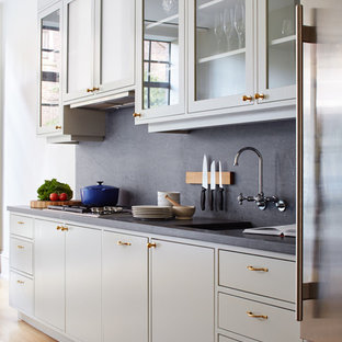This is an example of a mid-sized traditional galley eat-in kitchen in New York with flat-panel cabinets, grey splashback, brown floor, no island, concrete benchtops, an integrated sink, grey cabinets, stone slab splashback and medium hardwood floors.