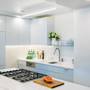 Ejemplo de cocina de galera, contemporánea, pequeña, con fregadero bajoencimera, armarios con paneles lisos, puertas de armario azules, salpicadero blanco, salpicadero de azulejos de porcelana, electrodomésticos de acero inoxidable y una isla