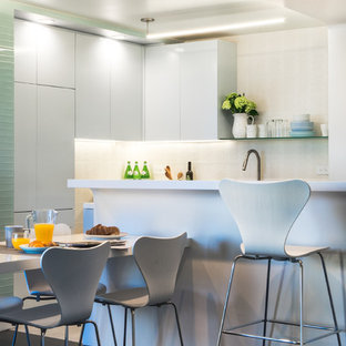 Small midcentury galley eat-in kitchen in New York with an undermount sink, flat-panel cabinets, grey cabinets, solid surface benchtops, white splashback, porcelain splashback, stainless steel appliances, porcelain floors and with island.