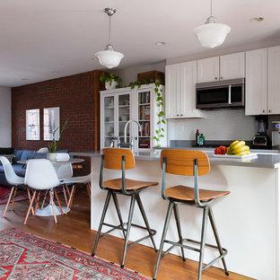 ニューヨークの小さいエクレクティックスタイルのおしゃれなキッチン (シェーカースタイル扉のキャビネット、白いキャビネット、クオーツストーンカウンター、白いキッチンパネル、サブウェイタイルのキッチンパネル、シルバーの調理設備の、グレーのキッチンカウンター) の写真