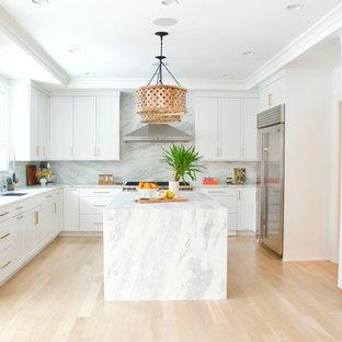 ニューヨークの中サイズのコンテンポラリースタイルのおしゃれなキッチン (フラットパネル扉のキャビネット、中間色木目調キャビネット、ソープストーンカウンター、グレーのキッチンパネル、淡色無垢フローリング、アンダーカウンターシンク、石スラブのキッチンパネル、シルバーの調理設備、ベージュの床) の写真