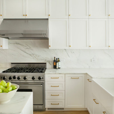 Inspiration for a mid-sized contemporary l-shaped eat-in kitchen remodel in New York with a farmhouse sink, shaker cabinets, white cabinets, marble countertops, white backsplash, marble backsplash, stainless steel appliances, an island and white countertops