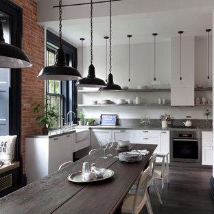 ニューヨークのインダストリアルスタイルのおしゃれなダイニングキッチン (エプロンフロントシンク、シェーカースタイル扉のキャビネット、白いキャビネット、シルバーの調理設備の、濃色無垢フローリング、アイランドなし、コンクリートカウンター) の写真