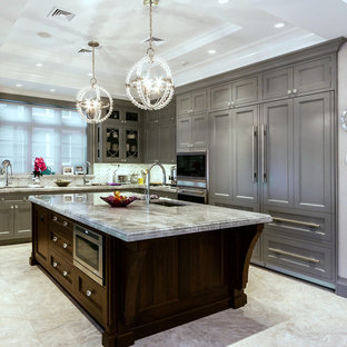 Photo of a large traditional kitchen in New York with integrated appliances, recessed-panel cabinets, grey cabinets, marble worktops, an island, a submerged sink, grey splashback and white floors.