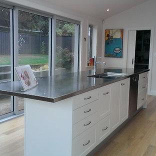 ウェリントンの中くらいのコンテンポラリースタイルのおしゃれなキッチン (一体型シンク、シェーカースタイル扉のキャビネット、白いキャビネット、ステンレスカウンター、白いキッチンパネル、サブウェイタイルのキッチンパネル、シルバーの調理設備、無垢フローリング、緑の床) の写真