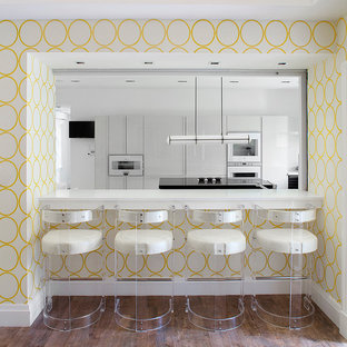 This is an example of a contemporary kitchen in New York with flat-panel cabinets, white cabinets and white appliances.