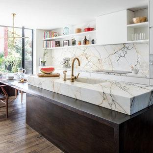 На фото: параллельная кухня среднего размера в скандинавском стиле с монолитной раковиной, плоскими фасадами, белыми фасадами, мраморной столешницей, разноцветным фартуком, фартуком из мрамора, темным паркетным полом, островом, коричневым полом, белой техникой, разноцветной столешницей и барной стойкой с