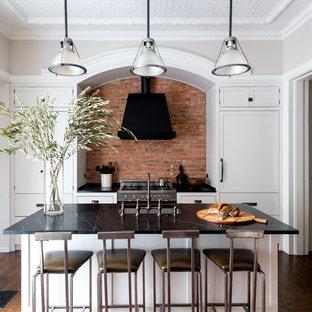 Einzeilige, Mittelgroße, Geschlossene Klassische Küche mit Unterbauwaschbecken, Speckstein-Arbeitsplatte, Rückwand aus Backstein, Kücheninsel, braunem Boden, Schrankfronten im Shaker-Stil, weißen Schränken, Küchenrückwand in Rot, Elektrogeräten mit Frontblende, dunklem Holzboden und schwarzer Arbeitsplatte in New York